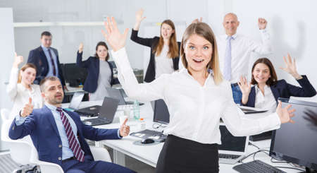 Successful business group with smiling woman foreground in coworking space