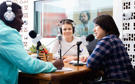 Multinational group of cheerful young adults emotionally discussing in radio studio Imagens