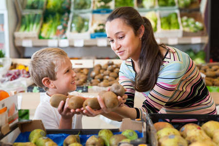 Portrait of happy woman and her little son choosing kiwi at shop