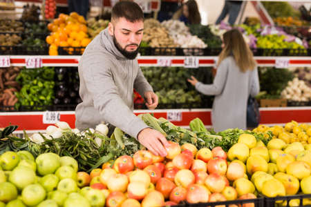 Male buyer is choosing apples in the grocery store