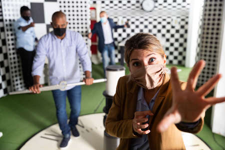 Woman in protective mask solves a puzzle in quest room Stock Photo