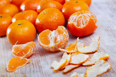 Closeup of fresh peeled clementines on wooden table