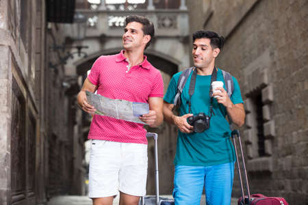 Portrait of two friends who are walking with map and suitcases a
