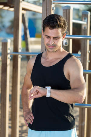 Athletic man looking at watch