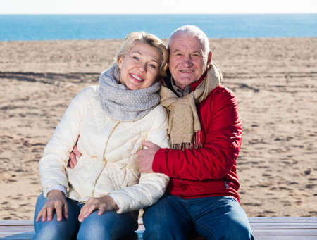 Mature couple sitting by sea