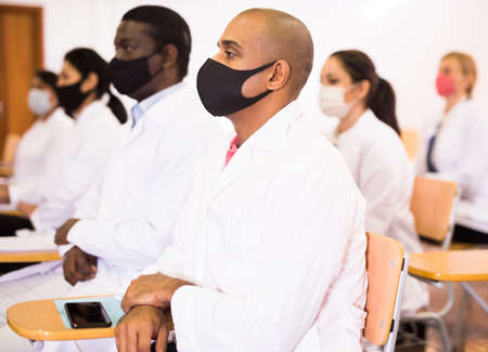 Hispanic doctor in protective mask attending medical congress