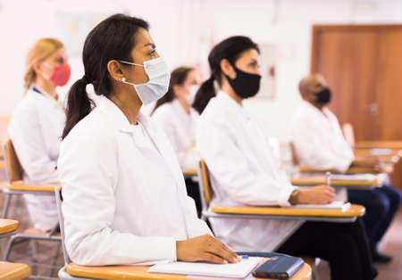 Hispanic woman in protective mask participating in medical congress