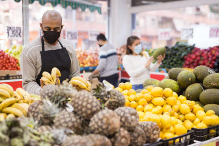 Latino-american worker in medical mask in supermarket during COVID-19 pandemic