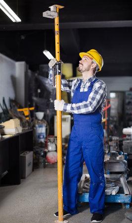 Young smiling man erecting framing at workshop
