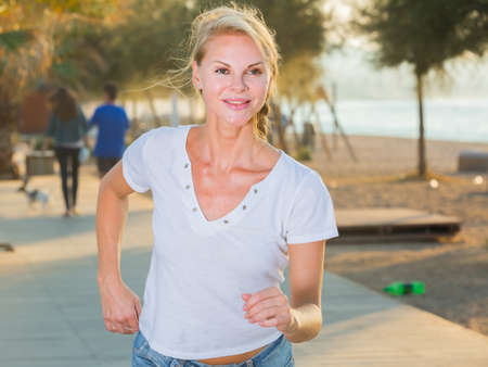 Female in white T-shirt is jogging