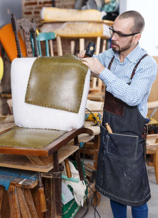 Craftsman reupholstering chair in workshop