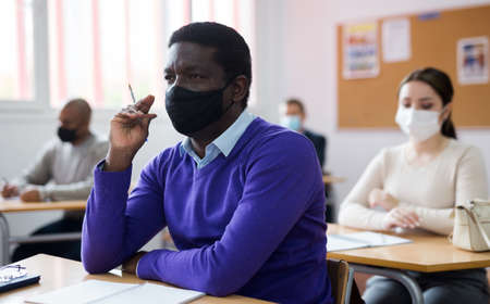African-american student wearing protective mask among students in classroom