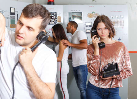 Young friends inspecting old telephone in quest room Stock Photo