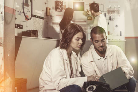Girl and guy checking battery charger in escape room