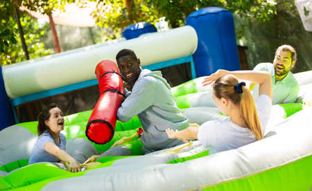 Funny friends playing on an inflatable trampoline in an amusement park