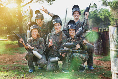 Portrait of paintball players wearing uniform and holding guns r