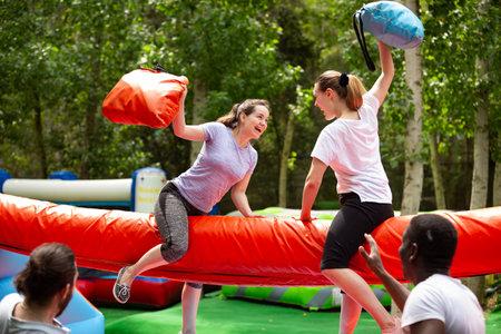 Pillow fight between girlfriends in an amusement park Imagens