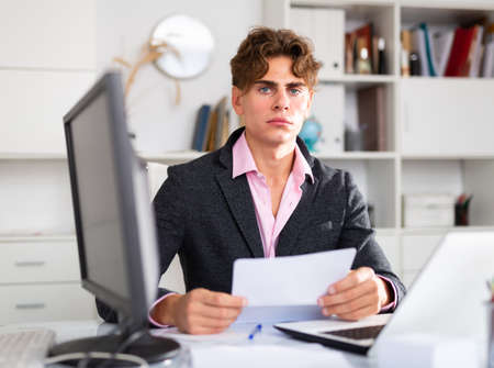 Upset attractive young businessman working documents and laptop