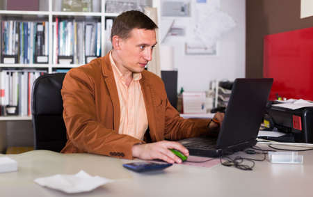 Portrait of concentrated manager working in agency office