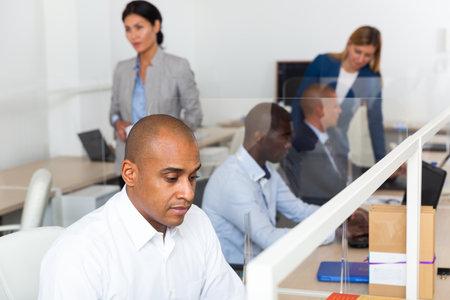 Hispanic entrepreneur working in modern busy coworking space