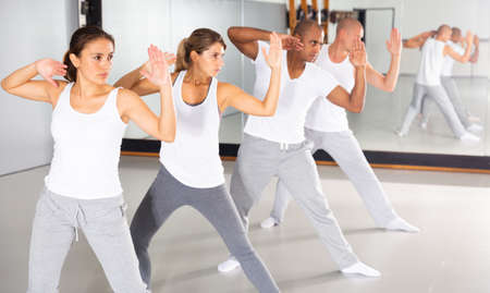 Men and women train in self defense courses in gym