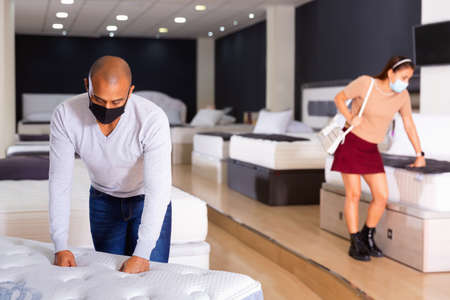 Latin american man in protective mask choosing new comfortable mattress at furniture store.