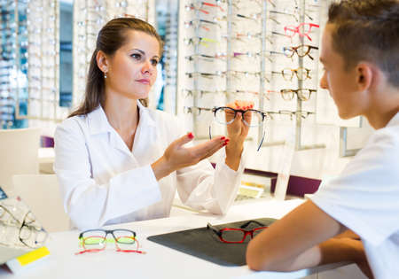 Ophthalmologist and cheerful young boy choosing glasses