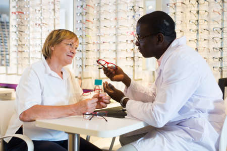 African American ophthalmologist consulting elderly woman