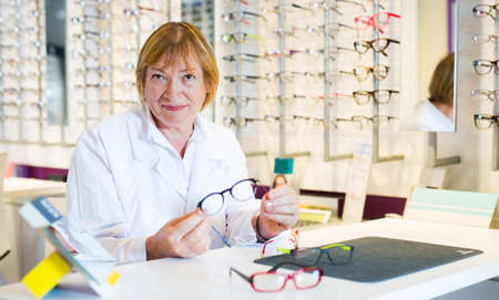 Professional senior female optician offering glasses in store