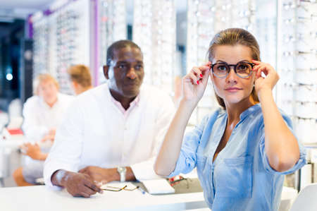 Woman trying on a spectacles in medical shop, male optician