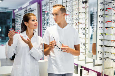 Young female ophthalmologist helping teen boy to choose glasses in optical store