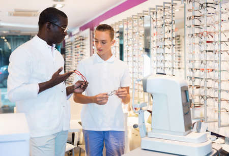 Teenage boy looking for stylish glasses with qualified African-American optician in optical shop