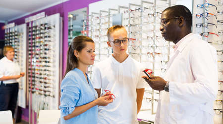 Young man and woman clients talking with ophthalmologist