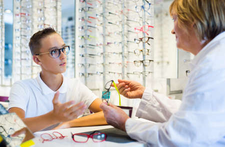 Teenage boy looking for glasses with aged woman optician Zdjęcie Seryjne