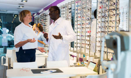 Ophthalmologist helping mature woman to choose glasses