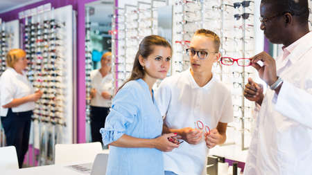 Male and female looking glasses frames, ophthalmologist helping Zdjęcie Seryjne