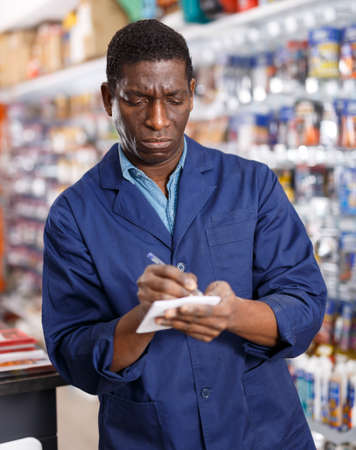 Adult African American workman making list