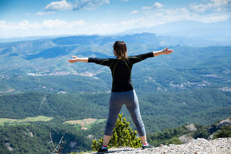 Rear view of female with raised hands on top of mountain Stock fotó