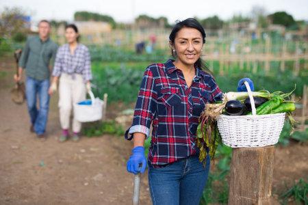 Happy hispanic woman showing vegetable crop in kitchen garden