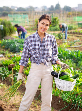 Happy woman gardener carrying basket with harvested vegetables