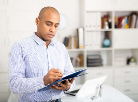 Businessman makes notes in the document at office