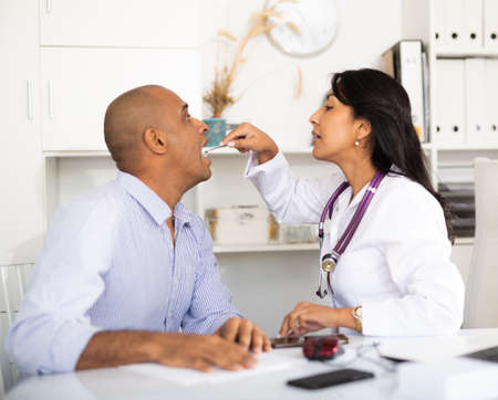Female doctor examining throat of patient in medical office