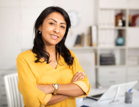 Happy smiling Latin American businesswoman standing in office Banque d'images