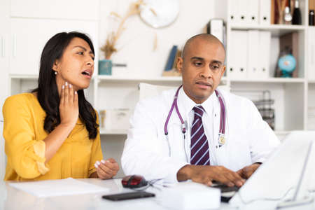Doctor consulting woman patient complaining of sore throat