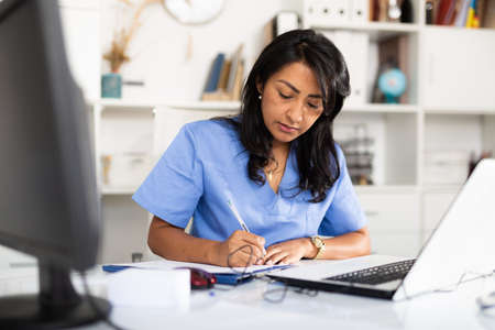 Focused female doctor working with laptop in clinic office
