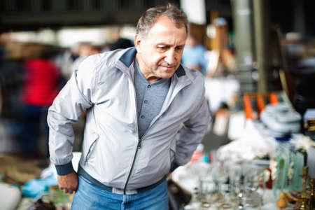 Positive elderly man choosing interesting souvenirs at traditional flea market Stockfoto