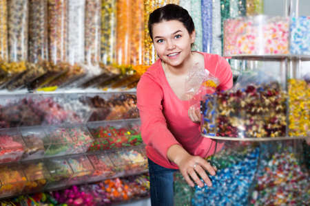 Woman in store is picking up candies
