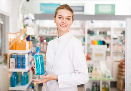 Smiling young pharmacist ready to assist in choosing at counter in pharmacy