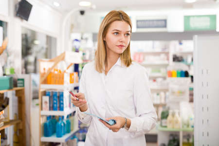 Pharmacist is writing down assortment of drugs in pharmacy