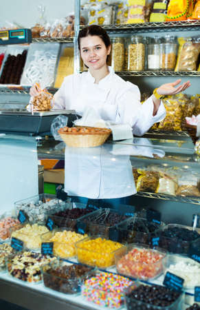Girl in uniform selling candied fruits and nuts Archivio Fotografico